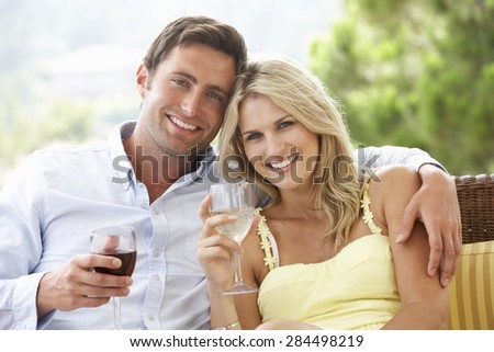 Couple Sitting On Outdoor Seat Together - stock photo