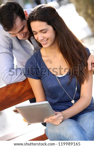 Couple sitting on public bench and using tablet
