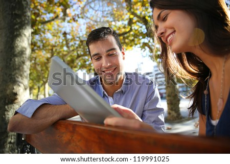 Couple sitting on public bench and using tablet - stock photo