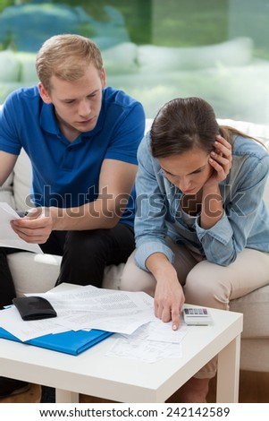 Couple sitting on sofa and analyzing home budget - stock photo