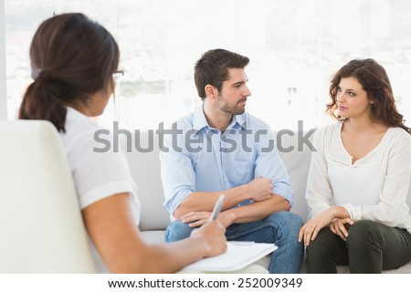 Couple sitting on sofa talking with their therapist in the office - stock photo