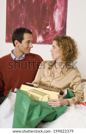 Couple sitting on sofa, unwrapping Christmas present, face to face - stock photo