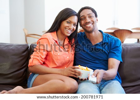 Couple Sitting On Sofa Watching TV Together - stock photo
