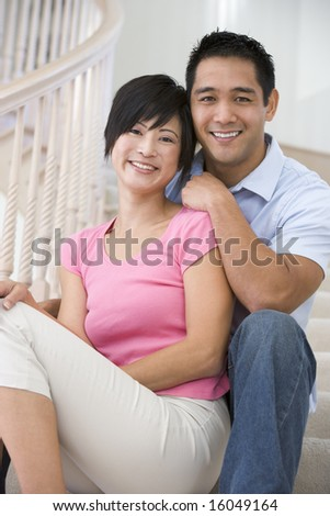 Couple sitting on staircase smiling - stock photo