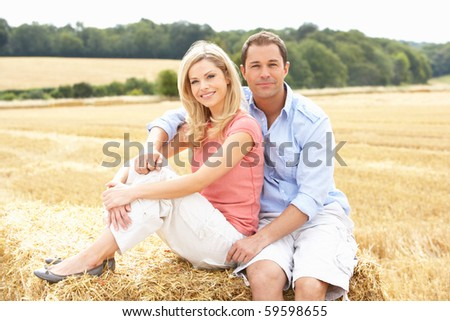 Couple Sitting On Straw Bales In Harvested Field - stock photo