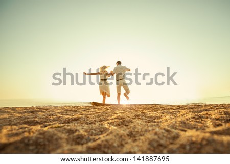 couple sitting on the beach at sunrise - stock photo