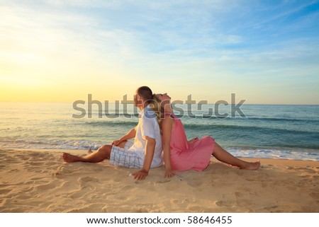 Couple sitting on the beach at sunrise time. - stock photo