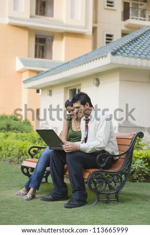 Couple sitting on the bench and using a laptop - stock photo