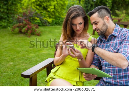Couple sitting on the bench in the garden and using smartphone and tablet