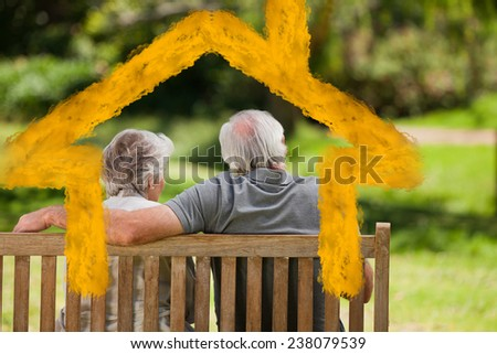 Couple sitting on the bench with their back to the camera against house outline in clouds - stock photo