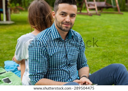 Couple sitting on the blanket back to back in the garden - stock photo