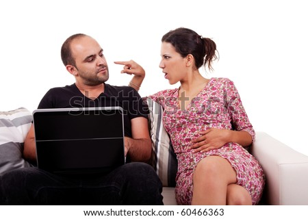 couple sitting on the couch, he playing computer and she argues with him, isolated on white, studio shot - stock photo