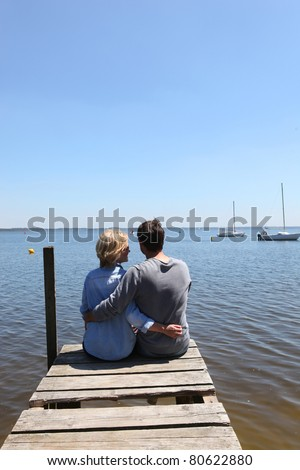 Couple sitting on the end of a pontoon with their arms around each other - stock photo