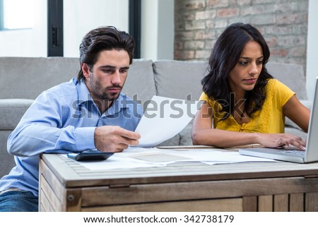 Couple sitting on the floor in living room paying bills - stock photo