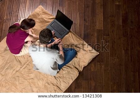 Couple sitting on the floor looking at a laptop screen together. Horizontally framed shot taken from above the subjects. - stock photo