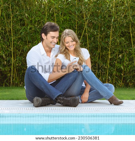 Couple sitting on the grass by the pool checking the smart phone - stock photo