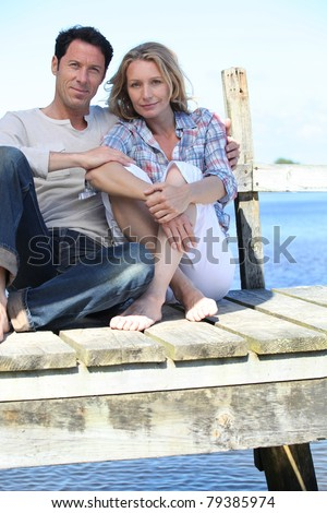 Couple sitting on the pier - stock photo
