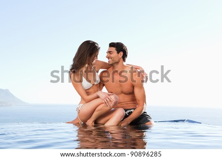 Couple sitting on the pool edge together - stock photo