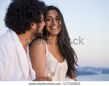 Couple sitting outdoors with champagne flutes and snuggling against scenic background