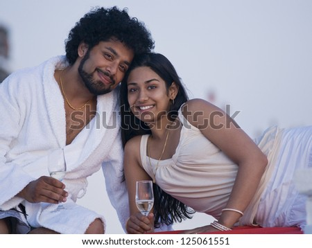 Couple sitting outdoors with champagne flutes smiling and snuggling