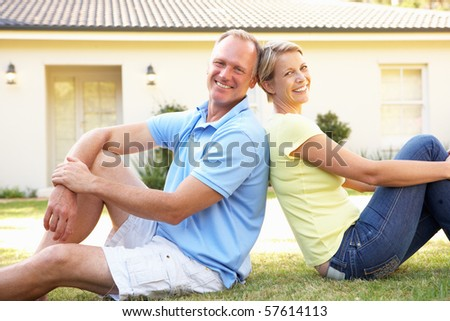 Couple Sitting Outside Dream Home - stock photo