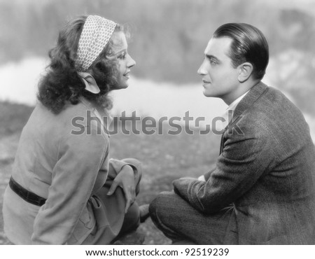 Couple sitting together and looking at each other - stock photo