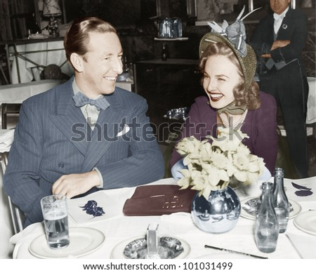Couple sitting together at a table having fun - stock photo