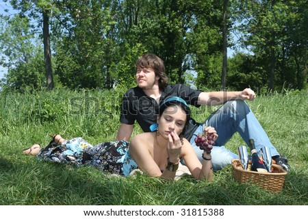 Couple sitting together by a lake with a picnic basket.