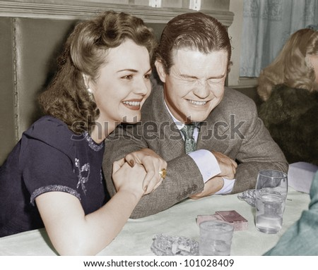 Couple sitting together laughing and happy - stock photo