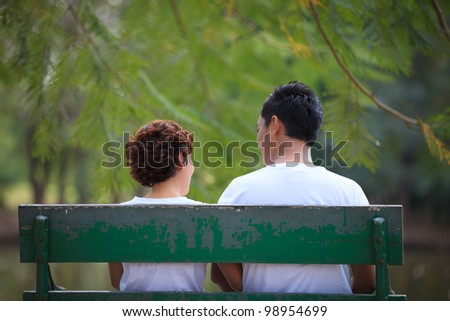 Couple sitting together on park - stock photo