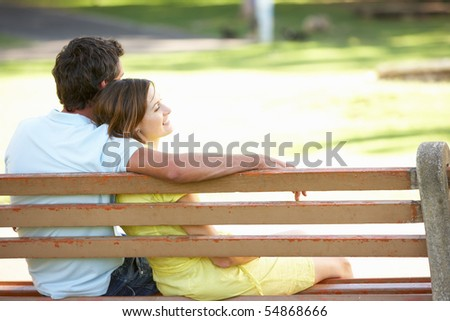 Couple Sitting Together On Park Bench - stock photo