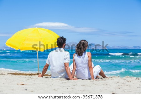 Couple sitting together on the beach and looking out at ocean.