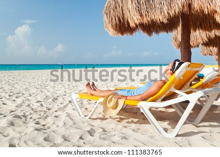 Couple sitting under palm tree at Caribbean Sea - stock photo