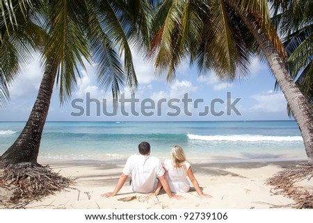 couple sitting under the palm trees in tropical beach - stock photo