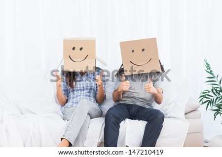 Couple sitting with cardboard boxes with smiley faces on head giving thumbs up in living room - stock photo