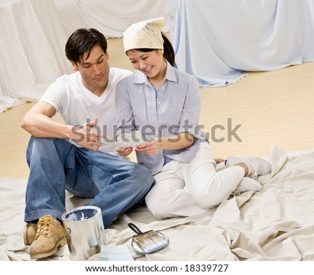 Couple sitting with paint can and color swatch preparing to decorate home interior - stock photo