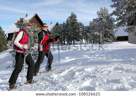 Couple skiing by chalets