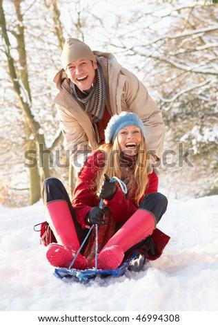 Couple Sledging Through Snowy Woodland - stock photo