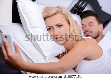Couple sleeping in bed. Young blonde woman, use your phone in while her husband sleeps - stock photo