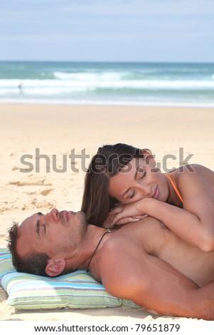 Couple sleeping on the beach - stock photo