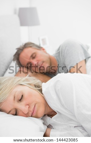 Couple sleeping peacefully at home in bed
