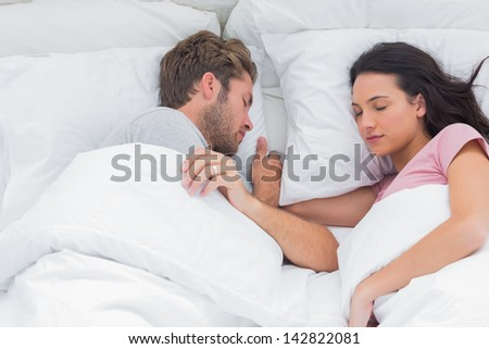 Couple sleeping peacefully in bed - stock photo