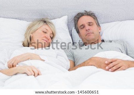 Couple sleeping peacefully in their bed at home in bedroom - stock photo