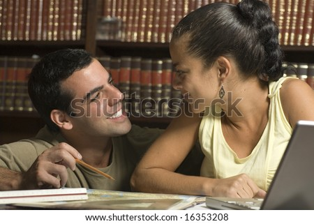 Couple smiles at each other in library. Man is kneeling and woman is sitting in front of laptop. Horizontally framed photo. - stock photo