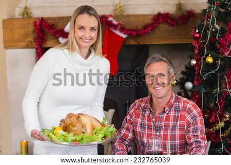 Couple smiling at camera while woman holding roast turkey at home in the living room - stock photo