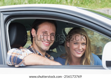 Couple smiling at the camera in their car - stock photo