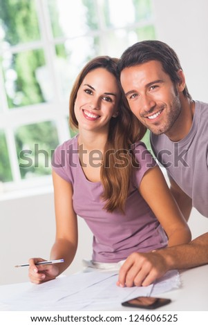 Couple smiling at the camera with invoices and phone - stock photo