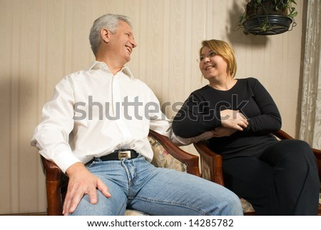 Couple smiling lovingly at each other, holding hands romantically. Horizontally framed shot. - stock photo