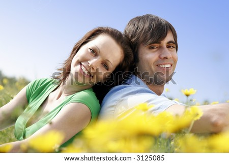 couple smiling,sitting in a flower-field