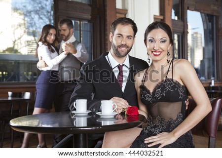 Couple Smiling While Dancers Performing Tango At Restaurant